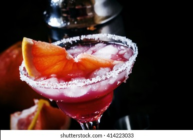Grapefruit daiquiri with salt, metal shaker, black background, selective focus