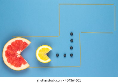 Grapefruit eating lemon, and lemon eating strawberries. Fruit composition. Fruit pursue fruit. Vitamins Good. Healthy food with fruit. Bright fruit on the blue background.