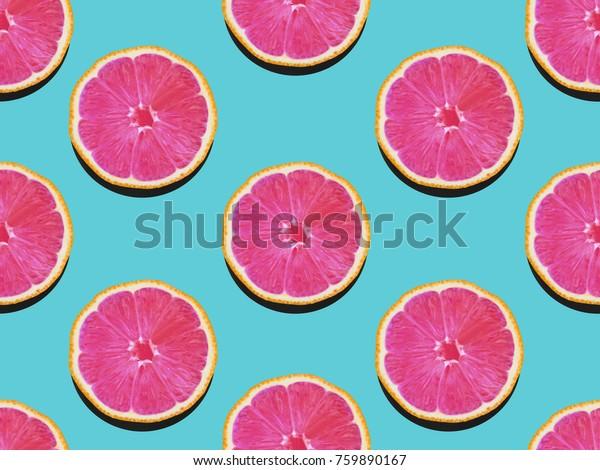 Грейпфрут в плоской кладке Фруктовый узор из грейпфрута с розовой мякотью на бирюзовом фоне Вид сверху Современный плоский рисунок фото в стиле поп-арт