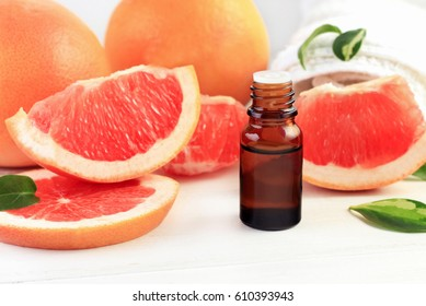Grapefruit fragrance oil in apothecary dark glass dropper bottle of liquid cosmetic product, fresh pink citrus fruit pulp in pieces. Sweet natural aromatherapy spa and health care