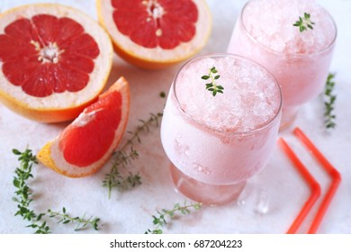 Grapefruit granita, frozen summer dessert in two glasses and fruits, selective focus