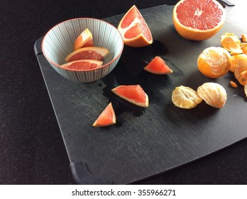 Grapefruit half and slices in bowl on black cutting board with clementines