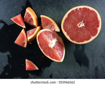 Grapefruit half and slices on black cutting board