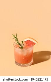 Grapefruit juice garnish rosemary sprig on color beige background. Mocktail Paloma. Close up. Vertical format.