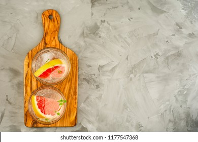 Grapefruit lemonade. Two glasses of detox drink, water with grapefruit, rosemary branches and ice. Recipe concept, cocktail