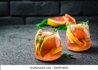 Grapefruit lime mocktail with rosemary and ginger on dark concrete background. Selective focus, copy space.