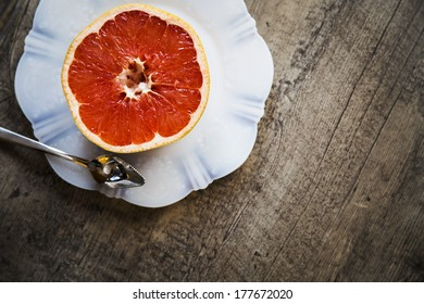 Grapefruit on a white plate on a wood background with spoon