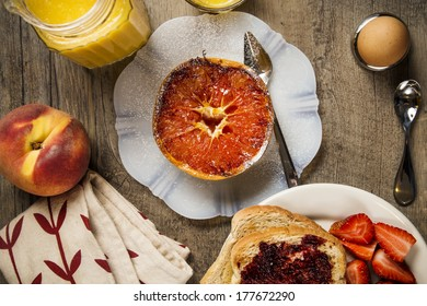 Grapefruit on a white plate on a wood background with spoon, orange juice, napkin, toast, soft boiled egg, toast, strawberries, and a peach