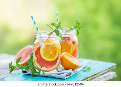 Grapefruit and orange water in glass jars in the open air. Concept for healthy eating and nutrition. Copy space.