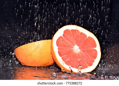 grapefruit in the rain in front of a black background