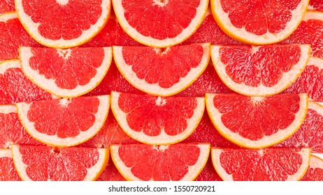 Grapefruit red juicy slices background. top view.