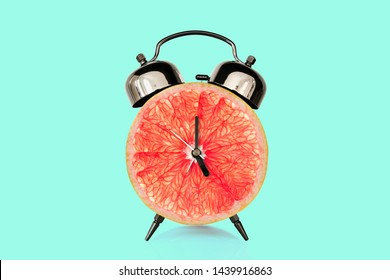 Grapefruit slice on alarm clock, blue pastel background. fruit and vitamins diet at breakfast nutrition concept