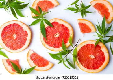 Grapefruit slices and marijuana leaves on white