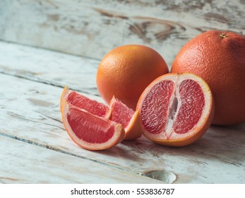 Grapefruit with slices on a wooden table, close up