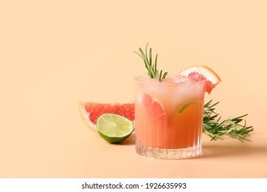 Grapefruit soda with lime garnish rosemary sprig on color beige background. Mocktail Paloma. Close up.