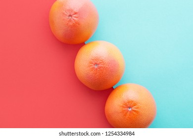 Grapefruits on Living Coral & pastel blue color diagonal background. Minimal summer concept flat lay. Year 2019