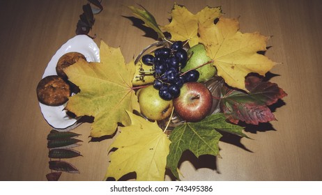 Grapes, apple, pear on a plate decorated with autumn leaves and cheese muffins next to them on wooden table