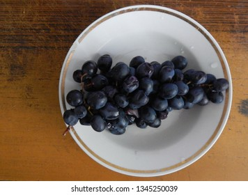 Grapes of black color lies on a plate