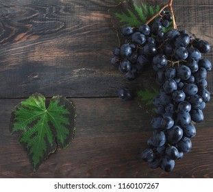 Grapes bunch with leaves on a old wooden background. Top view , copy space .