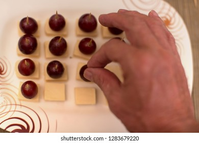 Grapes and cheese as toothpick snack  and stick appetizer with a mans hand  picking a tasty snack