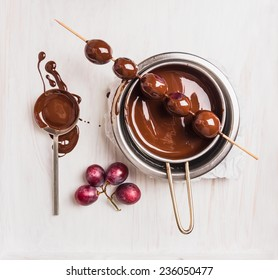 Grapes in chocolate making on white wooden background, top view