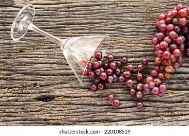 Grapes and glass lay on the wooden floor.