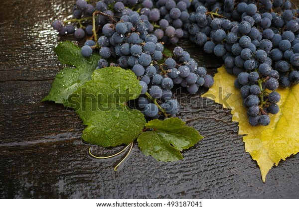 Grapes and grape leaves on a wet board.