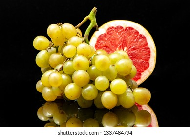grapes and grapefruit black background