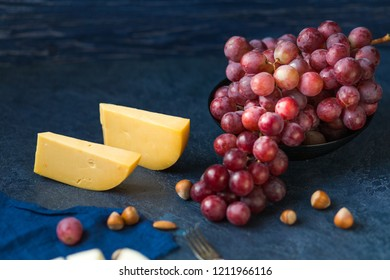 Сheese with grapes on a blue background