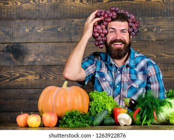 Grapes from own garden. Farming concept. Farmer proud of grapes harvest. Man hold grapes wooden background. Farmer bearded guy with homegrown harvest grapes put on head. Fresh organic harvest.