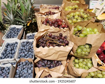 Grapes, pineapples and berries at an organic market stall.