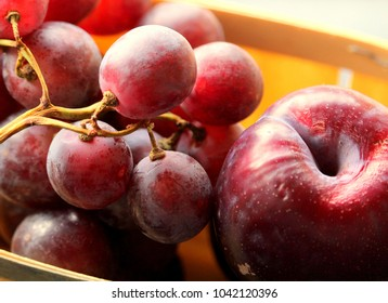 grapes and plums in wooden packing