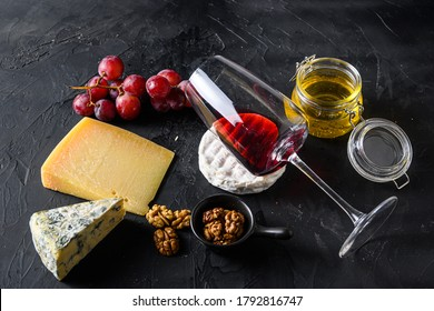 Grapes, red wine, cheeses, honey and nuts side view red merlot wine in glass antipasto