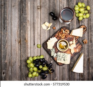 Grapes, red wine, cheeses, honey and nuts over rustic weathered wood. Top view with copy space.