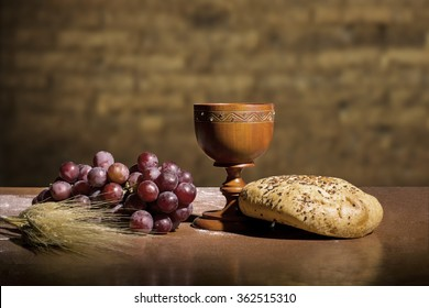 grapes, wheat, bread and wine in a wood table