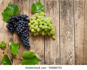 Grapes white and blue on a wooden background