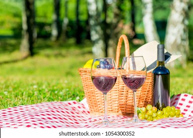 Grapes and wine, basket on a tablecloth in the park - objects for a picnic