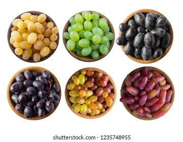 Grapes in a wooden bowl isolated on white background. Blue, yellow, red and green grapes on white background. Top view. Set of different grape varieties. Set of different grapes.