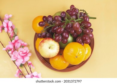 Grapes,Oranges and Apples put on Clay dish,beside blurred pink flowers,pastelbackground