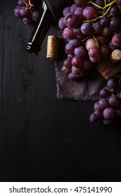 Grapevine on a wooden board. French vineyard. Wine bottle and cork. Dark wood background.