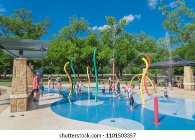 GRAPEVINE, TX, USA-May 28, 2018:Diverse kids enjoy water splash pad or sprayground at Parr Park. Water fountain activities during summer time. Covered pavilion, trees provide shade for parents