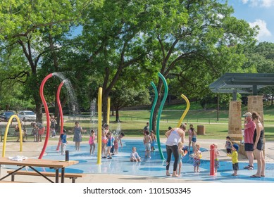 GRAPEVINE, TX, US-May 28, 2018:Diverse kids enjoy water splash pad or sprayground at Parr Park. Water fountain activities for child and parent during summer time. Outdoor healthily children activity