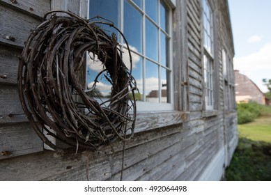 A grapevine wreath on the window of an old farmhouse. Barn in distance.