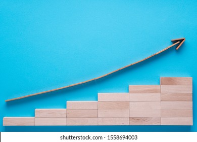 Graph with going up arrow. Wooden arrow going up on blue background.