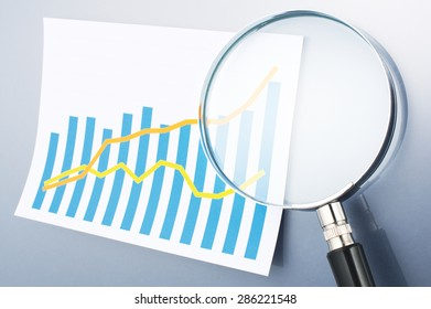 Graph and magnifying glass on gray background. Reading data. Looking graph with magnifying glass. Calculating, graphing and analyzing data.