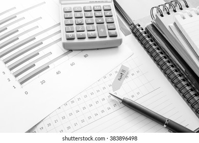 graph and note book on the wooden table with black and white color concept