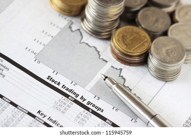 Graph Of Stock Market With Stacks Of Coins And Pen