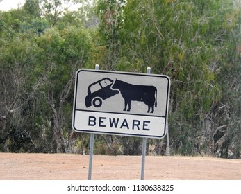Graphic Black and White Beware Cattle Crossing Road Sign showing a Car bumping into a Cow on the Savannah Way in remote Northern Queensland, Australia
