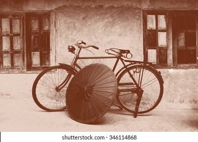 a graphic color of an old fashioned bicycle and vintage northern Thai umbrella in an old background