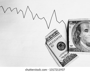 graphic with descending line and broken american banknote of 100 dollars